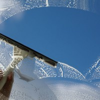 Window cleaner using a squeegee to wash a window